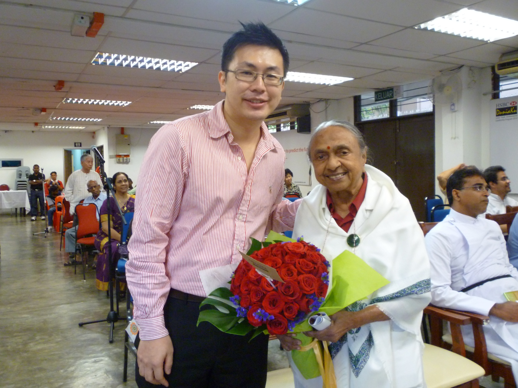 Presenting a bouquet of roses on behalf of Rinpoche to Mother Mangalam